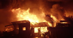 Fire consumes houses in Intense fire inferno in poor settlement Stock Footage
