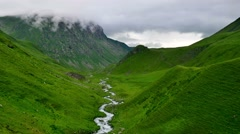 Timelapse of winding River and green valley in High Mountains with rising Clouds Stock Footage