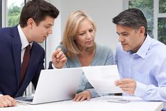 Mature Couple Meeting With Financial Advisor At Home Stock Photos