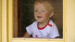 Funny little boy of 1,5 years idoors looks out the window and rejoices Stock Footage