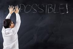 Boy with Impossible word on chalkboard - stock photo
