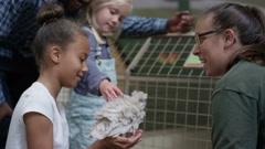 4K Man & little girls at community farm, petting chick & talking to keeper Stock Footage