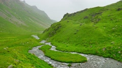 Mountain green valley and winding River on rainy day in Kavkaz region Stock Footage