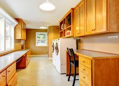 Spacious laundry room at the horse ranch. Furnished with storage combination  Stock Photos