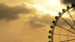 Ferris wheel gyrating at sunset at cloudy day - stock footage