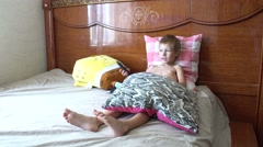 Boy with remote control watching TV, lying on the bed Stock Footage