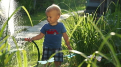 Funny little boy 1.5 years studying hosing plants in the garden Stock Footage
