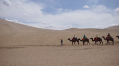 Tourists ride camels walking on desert at sunset, Dunhuang Stock Footage