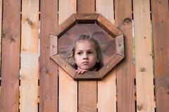 little girl looks out the window in a wooden house - stock photo