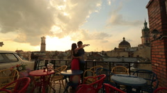 Young loving couple softly kissing on the rooftop cafe with ancient city view Stock Footage