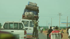 Van traveling with a man hanging behind, Africa. Video shots from a car Stock Footage