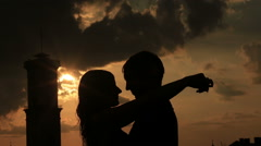 Silhouette of young loving couple softly kissing on the rooftop of ancient city - stock footage