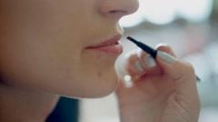 Professional makeup artist paints a model lips Stock Footage