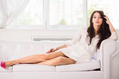 Charming brunette on the sofa Stock Photos