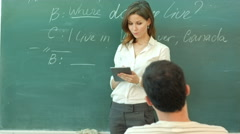 Female teacher with a tablet-pc held in her hands standing in front of the Arkistovideo