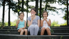 Sisters playing in the daubed ice creams noses together. Stock Footage
