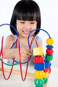 Asian Little Chinese Girl Playing Colorful Educational Toy - stock photo