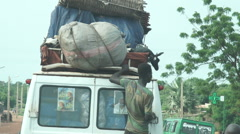 Africa, a van traveling with a man hanging behind and the goats on the roof Stock Footage