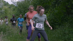 4K Competitors in endurance sports event running through tyre obstacle Stock Footage