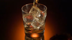 Single glass of whisky bourbon on ice on shiny background Stock Footage