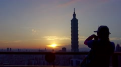4K Silhouette woman take photo with smart phone of Taipei 101 during sunset-Dan Stock Footage