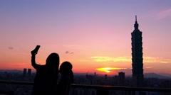 4K Silhouette Women take selfie picture with smart phone sunset Taipei 101 -Dan Stock Footage