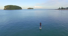 Aerial of whangamata beach paddleboarder, Coromandel, New Zealand Stock Footage