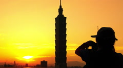 Silhouette woman take photo with smart phone of Taipei 101 during sunset-Dan Stock Footage