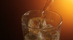 Barman pouring a scotch whiskey on the rocks, warm evening atmosphere Stock Footage