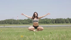 Slender girl practices yoga on the grass Stock Footage