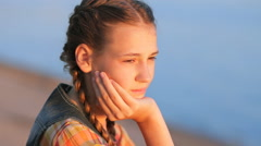 Sad teen girl resting chin in hand sitting on the beach Stock Footage