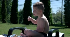 Caucasian Boy Eating Delicious Yogurt at the Park. Stock Footage