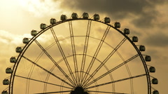 Silhouette of a ferris wheel in an amusement park spinning at sunset Stock Footage