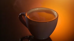 Black tea in blue cup with steam above on shiny background, warm evening Stock Footage