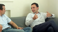 Two young male friend sitting on sofa and chatting at room. Men talk concept Stock Footage
