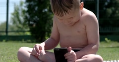 Little Boy Sitting on a Green Meadow With a Cellphone Stock Footage