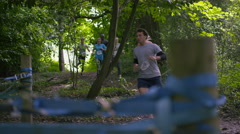 4K Competitors in assault course race helping each other over cargo net Stock Footage