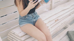 Young girl using phone with goblet of cocktail in hand on the beach bench in 4K Stock Footage