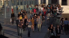 Young people walk and relax in trendy place on Patriarshy Bridge, evening time Stock Footage
