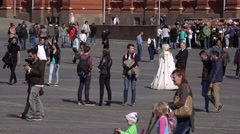 Unidentified people stroll at central square, telephoto shot of sightseers Stock Footage