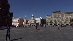 Asian, Caucasian tourists walk and make photos on Red Square, pan right Stock Footage