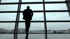 Man come and stand at full height, gaze out airport terminal window, silhouette Stock Footage