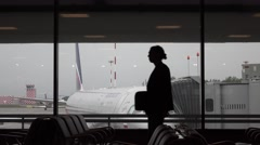 Man silhouette walk at terminal against window, large airliner parked outside Stock Footage