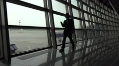 Man with cellphone quickly go towards, along glass wall window at airport Stock Footage
