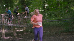 4K Competitors in assault course race, woman pauses for breath in foreground Stock Footage