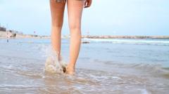 Woman legs walking on beach. Steadicam shot Stock Footage
