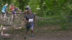 4K Competitors in assault course race, man pauses for breath in foreground Stock Footage