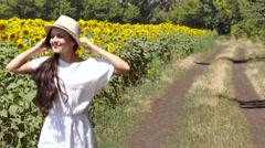 Woman runs across the road near a field of sunflowers Stock Footage