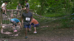 4K Competitors in assault course race, man pauses for breath in foreground Arkistovideo