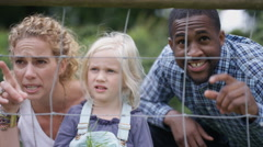 4K Portrait happy families at community farm looking into animal enclosure Stock Footage